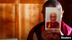 FILE - A monk holds a picture of Tibetan spiritual leader Dalai Lama inside of his room at Labrang Monastery in Xiahe county, Gansu Province.