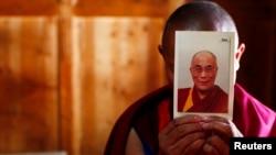 Seorang biksu membawa potret pemimpin spiritual Dalai Lama di Biara Labrang, Xiahe, Gansu (21/2/2012).