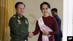 FILE - Myanmar's Commander-in-Chief Min Aung Hlaing, left, shakes hands with National League for Democracy party leader Aung San Suu Kyi before meeting in Naypyitaw, Dec. 2, 2015.