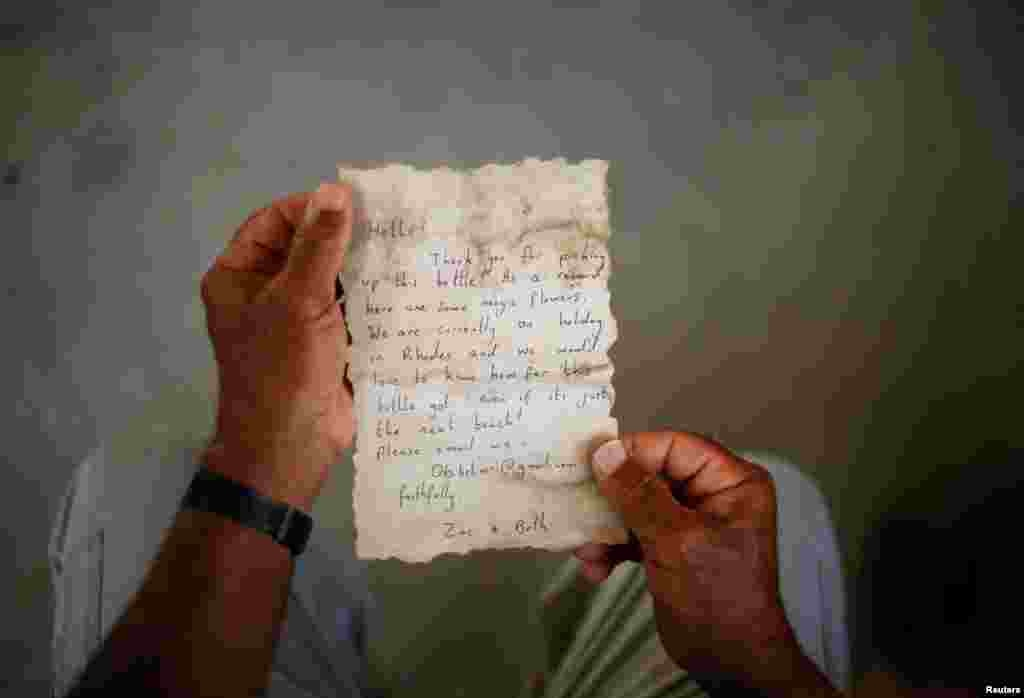 Palestinian fisherman Jihad al-Soltan displays a message that was written by Bethany Wright and her boyfriend Zac Marriner, after he found it in a bottle off a Gaza beach, Aug. 21, 2017.