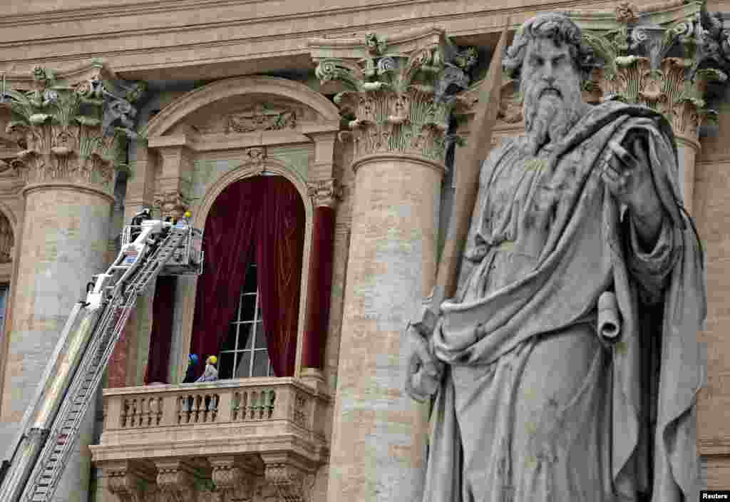 Workers put up a red curtain on the central balcony, called the Loggia of the Blessings, of Saint Peter's Basilica at the Vatican. Roman Catholic Cardinals begin a conclave Tuesday to elect the Church's 266th pontiff. After being elected in the conclave, the new pope will appear on the balcony.