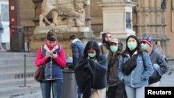 Para pengunjung mengenakan masker pelindung saat berjalan di Florence di tengah upaya pemerintah Italia memerangi wabah virus corona, Sabtu, 7 Maret 2020.