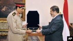 حسین طنطاوی، وزیر دفاع سابق (سمت چپ) در حال دریافت مدال از محمد مرسی، رئیس جمهوری وقت مصر - ۱۴ اوت ۲۰۱۲