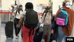 Pasajeros en el Aeropuerto Internacional de Miami caminan con mascarillas para tomar un vuelo para el día de Acción de Gracias. [Foto: Antoni Belchi, VOA]