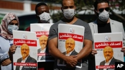 People hold posters of slain Saudi journalist Jamal Khashoggi, near the Saudi Arabia consulate in Istanbul, marking the two-year anniversary of his death, Oct. 2, 2020.