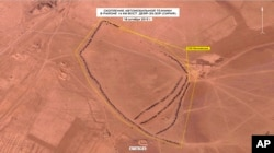In this photo made from video taken from Russian Defense Ministry official web site on Dec. 2, 2015, an aerial image of what they purport shows lines of oil trucks 14 km (8.8 miles) east of Dayr-az-Zawr, Syria.