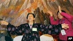 북측 리재선씨가 남측 동생 이천룡(우)씨와 함께 노래를 부르며 어깨춤을 추고 있다.