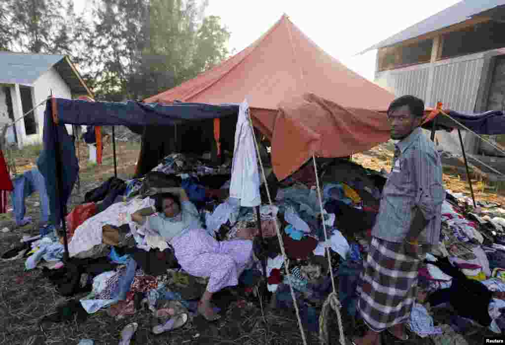 A Rohingya migrant woman who recently arrived in Indonesia by boat lies on a pile of donated clothes at a shelter in Kuala Langsa, Aceh Province, Indonesia, May 19, 2015.