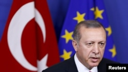 "FILE - Turkey's President Tayyip Erdogan at the European Union Commission headquarters in Brussels, Belgium. The EU noted Turkey's continued interest in joining the bloc, but said that was offset by some key legislation that ""ran against European standards."""