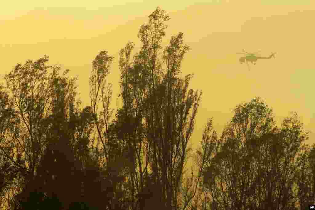 Un helicóptero lleva agua para lanzarlas a las llamas.