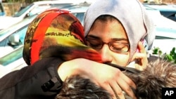 2015年2月12日美国北卡罗来纳州罗利市的民众在一座清真寺为三名遇害的穆斯林学生举行葬礼。图为两位穆斯林妇女在清真寺外面相拥哭泣