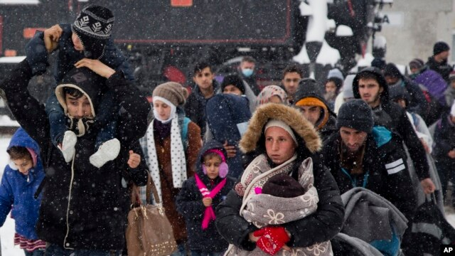 FILE - A group of migrants move through snow toward a train station to be transferred to Austria, near the border with Croatia, in Dobova, Slovenia, Jan. 3, 2016.
