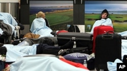 Passengers rest on the floor as their flights have been canceled at Edinburgh Airport in Edinburgh, Scotland, May 24, 2011