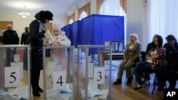 Seorang perempuan memberikan suaranya di TPS dalam pemilihan parlemen di Kyiv, Ukraina, 26 Oktober 2014.