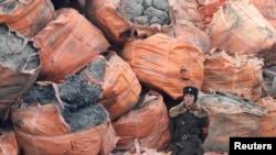 Seorang tentara Korea Utara berjaga di depan karung-karung berisi bijih mineral di tepi Sungai Yalu, dekat Kota Sinuiju Korea Utara yang berbatasan dengan Kota Dandong di China, 28 Desember 2011. (Foto:Dok)