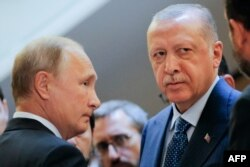 Russian President Vladimir Putin, left, and Turkish President Recep Tayyip Erdogan wait to enter a hall during their meeting at the Bocharov Ruchei residence in the Black Sea resort of Sochi, in Sochi, Sept. 17, 2018.