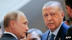 Ba Perezida w'Uburusiya na Vladimir Putin, ibiryo, n'uwa Turukiya Recep Tayyip Erdogan barindiriye kwinjira gusinya amasezerano. Itariki 17/09/2018.