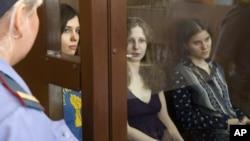 2012年8月8日俄罗斯女庞克摇滚乐队Pussy Riot的成员歌手托洛尼克娃(图左), 奥尔约其纳(图中),和萨姆泽维奇(图右)坐在俄罗斯一个法庭的一个拘禁她们的玻璃隔离的角落
