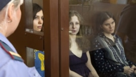 Feminist punk group Pussy Riot members, from left, Nadezhda Tolokonnikova, Maria Alekhina and Yekaterina Samutsevich sit in a glass cage at a court room  in Moscow, Russia, August 8, 2012.
