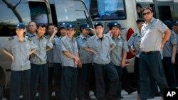 保安人员监视和阻止美联社记者拍摄中国政府人员拆毁浙江省永嘉县大沸下天主堂十字架。(2015年7月30日)