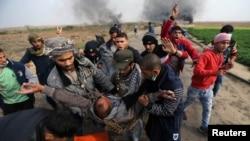 在加沙地带南部与以色列交界处,一名受伤的巴勒斯坦示威者被抬走。(2017年12月29日)