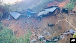 A landslide damages houses in a village in Phuoc Loc district, Quang Nam province, Vietnam Thursday, Oct. 29, 2020.