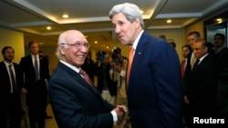 ລັດຖະມົນຕີຕ່າງປະເທດ ສະຫະລັດ ທ່ານ John Kerry ສຳພັດມືກັບ ທ່ານ Sartaj Aziz (ຊ້າຍ) ທີ່ປຶກສາດ້ານຄວາມປອດໄພແຫ່ງຊາດປາກິສຖານ.