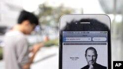 這名男子星期四在上海市中心的蘋果店外手持iPhone 4悼念喬布斯
