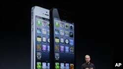 Apple CEO Tim Cook speaks in front of an image of the iPhone 5 during an Apple event in San Francisco, Sept. 12, 2012.