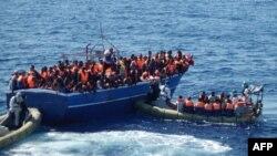 Trong bức hình được hải quân Italia công bố hôm 17/1/2014, những người dân di cư ngồi trên một chiếc thuyền quá tải được cứu ngoài khơi Sicily.