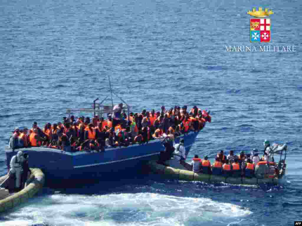 "In this handout picture released by the Italian navy, migrants sit on a overcrowded boat during a rescue operation off the coast of Sicily. Around 1,000 migrants has been rescued in the last 24 hours by ships engaged in the "" Mare Nostrum"" operation."