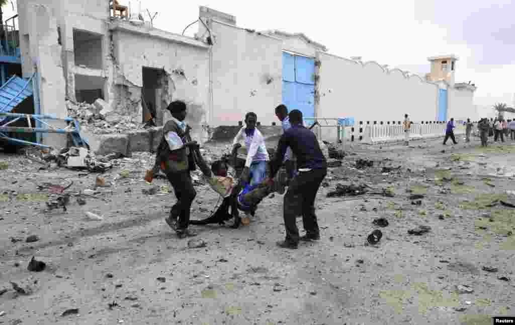 Somali government soldiers evacuate an injured man after a suicide bomb attack at a U.N. compound in Mogadishu, June 19, 2013.