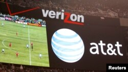 FILE - An advertisement for AT&T appears on a Verizon-branded scoreboard at New Meadowlands Stadium during a U.S.-Argentina soccer match in East Rutherford, N.J., March 26, 2011.