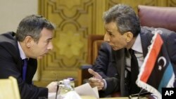 Ashour Abu-Rashed, right, Libyan representative at the Arab League, talks to his Egyptian counterpart, Tarek Adel, during an emergency meeting in Cairo to discuss the conflict in Libya, Jan. 5, 2015.