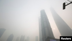 An electronic screen and buildings are seen amid heavy smog at the financial district of Pudong in Shanghai, Dec. 6, 2013.