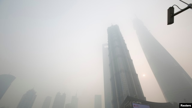 FILE - An electronic screen and buildings are seen amid heavy smog at the financial district of Pudong in Shanghai, Dec. 6, 2013.