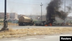 Burning vehicles belonging to Iraqi security forces are seen during clashes between security forces and al Qaida-linked Islamic State in Iraq and the Levant (ISIL) in the northern city of Mosul, June 10, 2014.