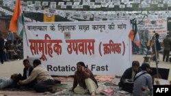Para demonstran duduk di depan spanduk memprotes pemerkosaan dan pembunuhan Desember lalu terhadap seorang perempuan di New Delhi (2/1)