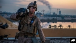 In this Saturday, Jan. 4, 2020, photo, released by the U.S. military, a U.S. Marine with 2nd Battalion, 7th Marines that is part of a quick reaction force, carries a sand bag during the reinforcement of the U.S. embassy compound in Baghdad, Iraq. (U.S. Marine Corps photo via AP)