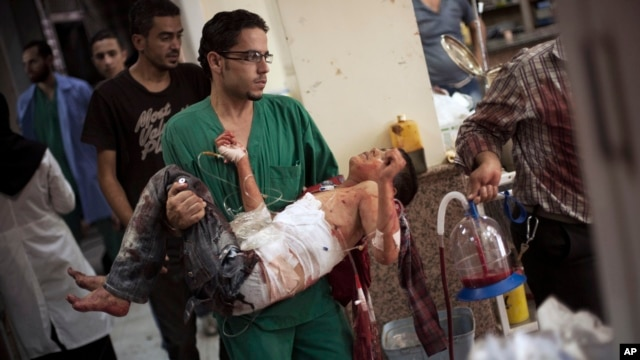 A doctor carries a severely wounded Syrian boy in the city of Aleppo.
