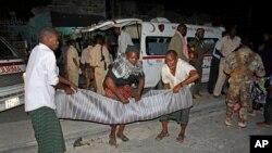 Warga di Mogadishu mengangkut korban tewas dalam ledakan di dekat cafe di Mogadishu (12/10).
