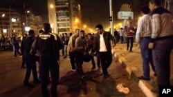 Anti-vladini demonstranti nose povređenog kolegu nakon sukoba sa pristalicama egipatskog predsednika u Kairu