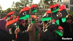Perempuan Libya ikut berpawai keliling kota dengan membawa bendera negaranya dalam perayaan dua tahun revolusi di Benghazi, 17 Februari 2013. (REUTERS/Esam Al-Fetori).