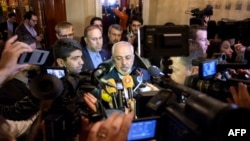 Iranian Foreign Minister Mohammad Javad Zarif, center, speaks to the press after meeting with the German and French foreign ministers in separate meetings at the Beau Rivage Palace Hotel in Lausanne, Switzerland, March 28, 2015.
