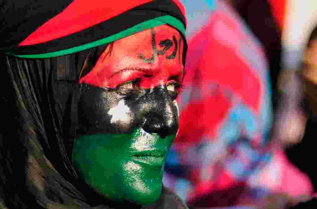 """June 29: A woman with her face painted in the colours of the Kingdom of Libya flag attends a protest against Muammar Gaddafi near the court house in Benghazi. The word on her forehead reads, """"Leave"""". (Reuters/Esam Al-Fetori)"""