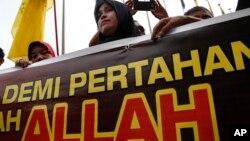 """Seorang perempuan muslim Malaysia membentangkan spanduk bertuliskan """"Allah"""" saat menggelar aksi protes di luar Pengadilan di Putrajaya, luar Kuala Lumpur, Malaysia, Senin (23/6)."""