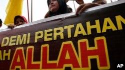 """2014年6月23日马来西亚穆斯林女子在上诉法院外举着""""安拉""""标语牌"""