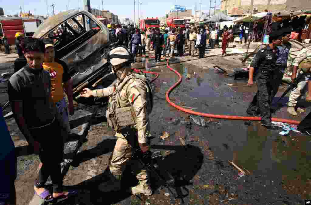 People and security forces inspect the site of a car bomb explosion in Basra, Iraq, July 29, 2013.