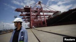 An employee stands next to a container ship at Ningbo port in Ningbo, Zhejiang province, June 21, 2012.