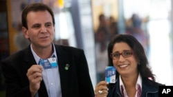 Nawal El Moutawakel, head of the IOC Evaluation Commission, right, and Eduardo Paes, Rio de Janeiro's Mayor, show tickets before boarding a Bus Rapid Transit (BRT) during the 3rd visit of the IOC Coordination Commission for the Rio Olympics 2016 in Rio de